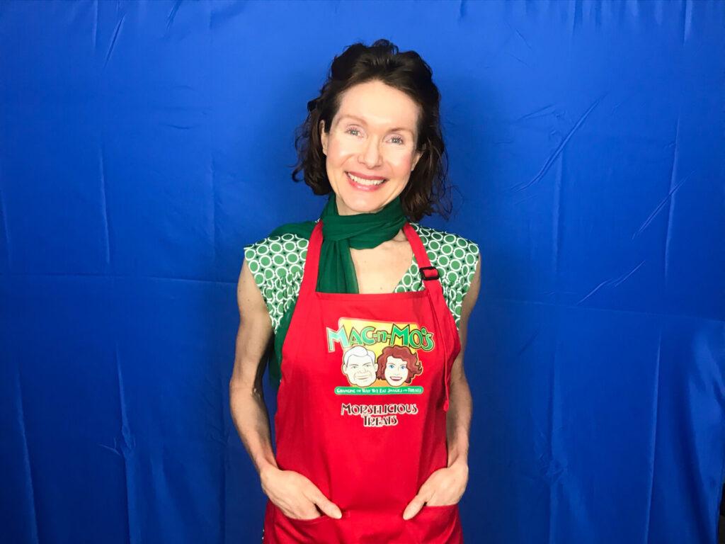 Health coach, Mo The Morselist, in a red Mac-n-Mo's apron against a blue backdrop